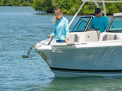 A woman drops an anchor on a 25' DC 246 Pursuit dual console boat.