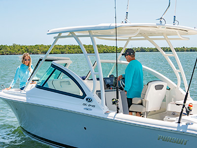 A couple enjoys a day on the water ready to fish or cruise on a 25' DC 246 Pursuit dual console boat.