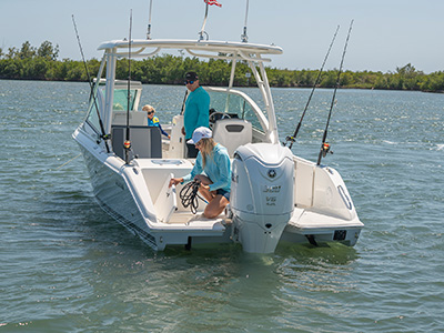 A woman placing a line in a transom storage compartment on a new DC 246 Pursuit dual console boat.