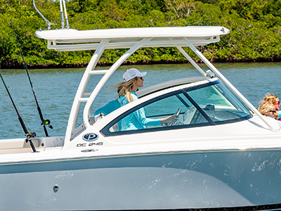 A woman is cruising at the helm of a DC 246 Pursuit dual console boat.
