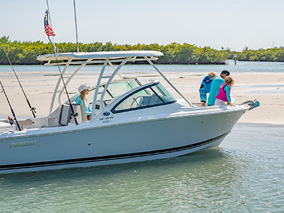A family is enjoying a day at the sandbar on a new DC 246 Pursuit dual console boat.