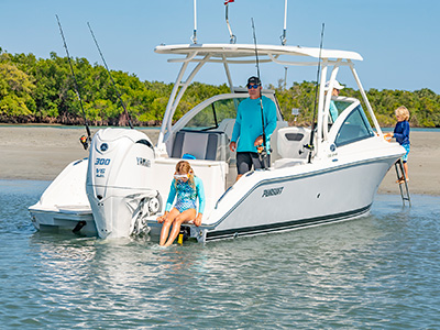 A family plays on a sandbar on a 25' DC 246 Pursuit dual console boat.