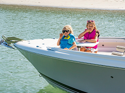 Children have a snack at a bow table on a 25' DC 246 Pursuit dual console boat.