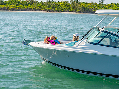 After a day of boating, a family relaxes on a sun pad aboard a DC 246 Pursuit dual console boat.