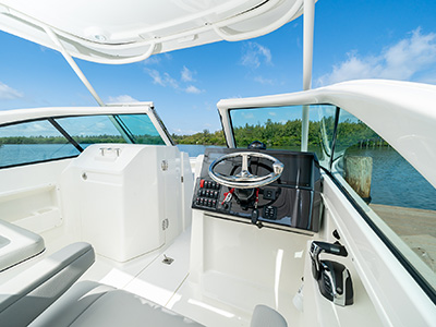 The helm of a DC 246 Pursuit dual console boat covered by an integrated fiberglass hardtop.