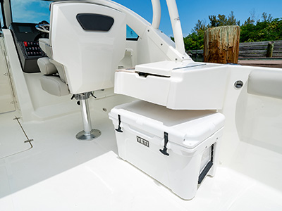 A closed wet bar and Yeti cooler for entertaining on a 25' DC 246 Pursuit dual console boat.