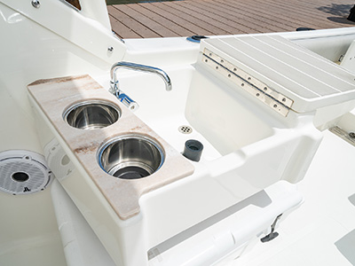 A cockpit wet bar with sink with faucet, two cupholders, Corian accent with fold out cutting board on a DC 246 Pursuit Dual Console Boat.
