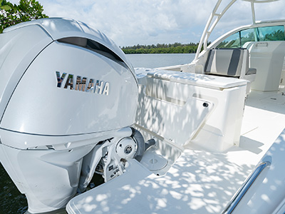 A large swim platform extends from the transom door on a DC 246 Pursuit Dual Console boat.