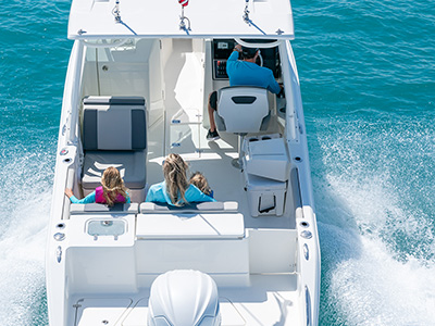 A stern angle view of DC 246 Pursuit Dual Console Boat with a family onboard.