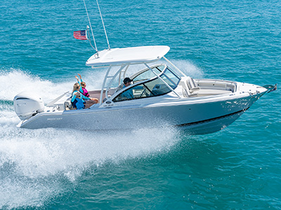 A starboard side exterior view of family fun on a DC 246 Pursuit Dual Console Boat running offshore.