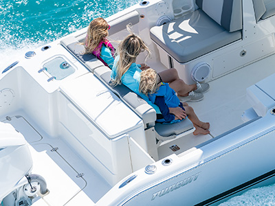 A family sits comfortably in foldaway transom seating on a 25' entry entry-level DC 246 Pursuit dual console boat.