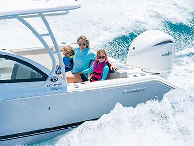 A smiling young family sits in foldaway seats in the back of a DC 246 Pursuit Dual Console Boat.