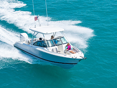 A girl enjoys riding on a bowrider DC 246 Pursuit dual console boat with hardtop.