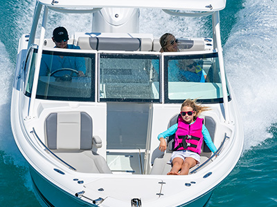 A DC 246 Pursuit dual console boat, family boat, with a girl sitting on bowrider seats.