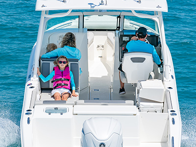 A family enjoys a ride on offshore on a DC 246 Pursuit dual console boat.