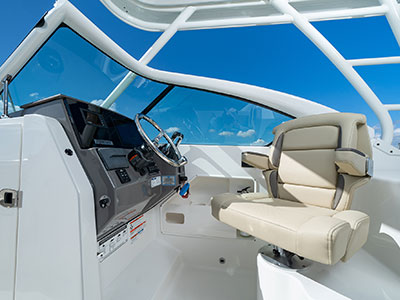 Bridge view of helm and helm seat of Pursuit DC 266 dual console boat.