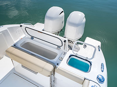 Aerial view of transom storage and fish box lids open of Pursuit DC 266 dual console boat.