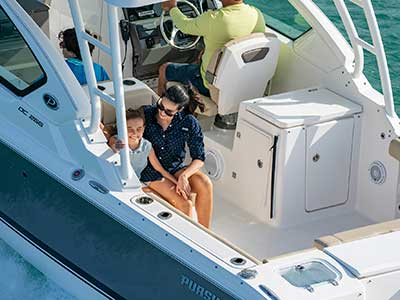Close up of mom and daughter sitting in cockpit of titanium Pursuit DC 266 dual console boat.