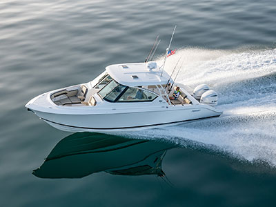 Aerial port side running shot of White Pursuit DC 295 family friendly Dual Console bowrider boat.