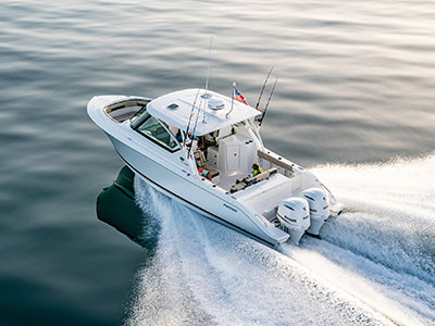 Aerial port side running shot of White Pursuit DC 295 with twin Yamaha engines and comfortable and innovative features.
