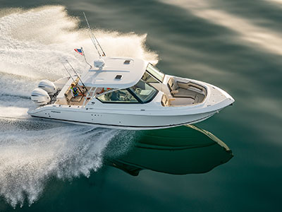 Aerial starboard side running shot of White Pursuit DC 295. The large tempered glass wrap-around windshield with opening center glass and bow block-off door provides superior weather protection with climate control.