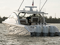 Rear view of white Pursuit DC 365 dual console boat on over cast day.