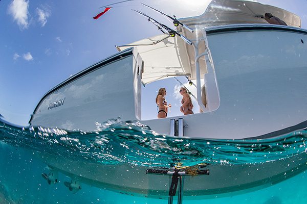 Looking up from water through S 408 side boarding door at 2 women inside boat