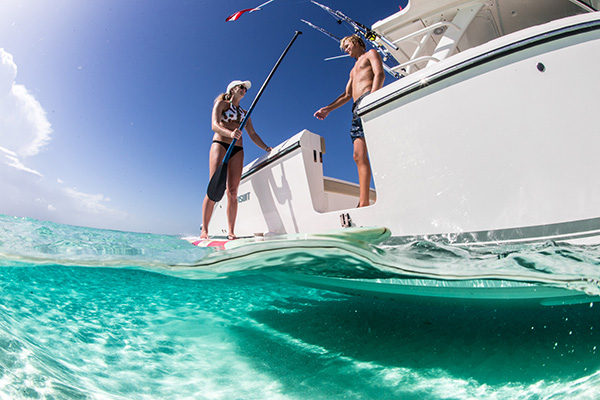 White S 408 in shallow water with side boarding door open and approaching paddle boarder