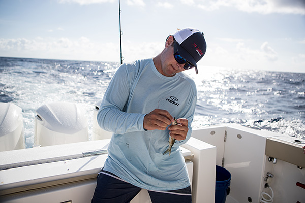 Man placing bait on fishing line in the cockpit