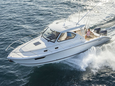 Aerial one quarter profile of white OS 325 Offshore cabin cruiser running left with guard rails and outriggers.