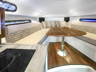OS 325 cabin V-berth seating with solid wood table and yacht style appointments.