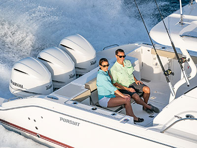 Aerial close up of couple sitting on transom seat of OS 355 cruising offshore.