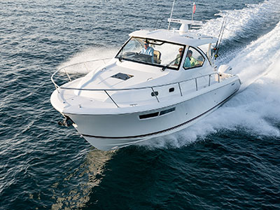 Aerial front one quarter view of white Pursuit OS 355 Offshore cabin cruiser.