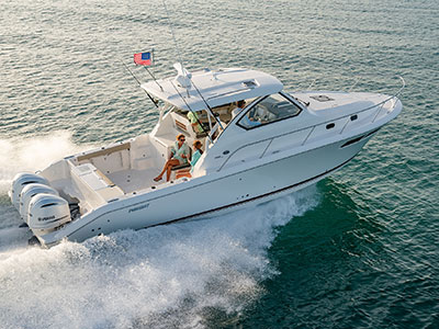 Aerial profile view of white OS 355 with liveaboard space and triple Yamaha outboard engines running right.