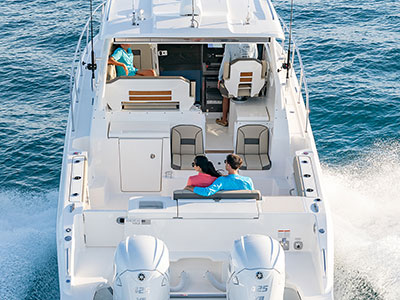 Aerial rear view of white OS 355 showing luxurious seating, social zones and twin outboard engines.