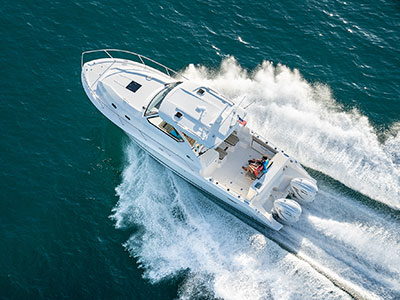 Aerial overhead view of white OS 355 offshore boat running left offshore with twin outboard engines.