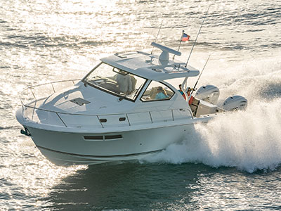 Aerial profile view of 32 foot OS 355 offshore boat running left with cabin window.