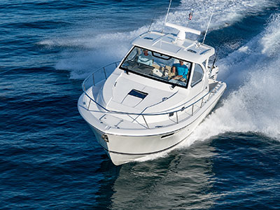 Aerial front one quarter view of white 32' Pursuit OS 355 with tempered windshield.