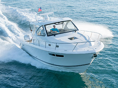 Aerial front one quarter view of white Pursuit OS 355 cruising and fishing boat.
