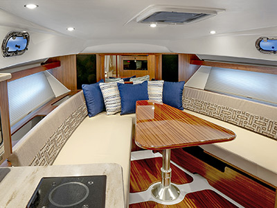 Detail view of OS 355 Galley area and V-berth seating with solid wood table.