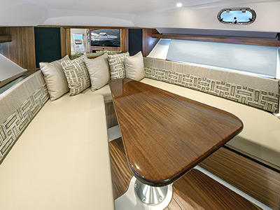 Detail view of OS 355 V-berth seating with solid wood table.