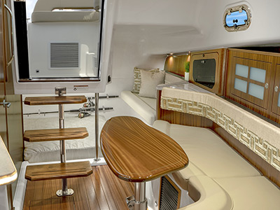 OS 385 cabin aft berth with solid wood table and seating.