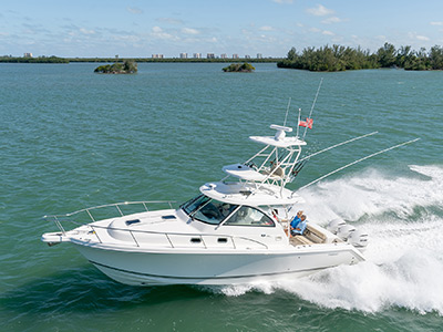 Aerial profile view of white 38 foot OS 385 Offshore boat with tower and outriggers cruising left.