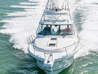 Aerial front view of white 38 foot OS 385 Offshore boat with tower running tempered glass weather protection.