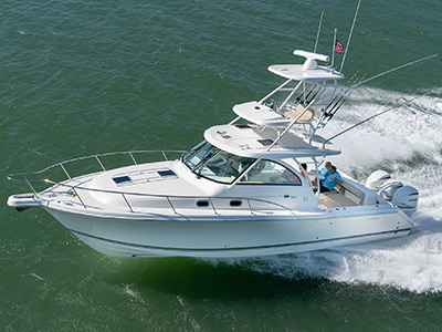 Aerial profile view of white OS 385 offshore boat with tower running left with rod holders, hardtop and tower.