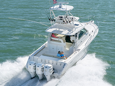 Aerial rear view of white OS 385 offshore boat with tower running right with triple Yamaha outboard engines.