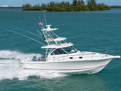 Aerial profile view of white 38 foot OS 385 Offshore cabin cruiser with fishing tower running right.