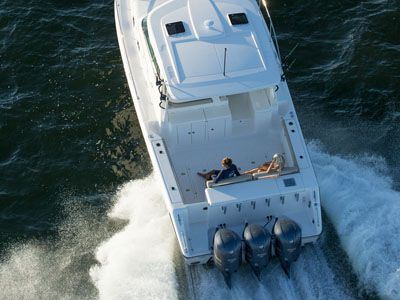 Rear aerial view of white 38 ft. OS 385 Offshore with hardtop and twin outboard engines.