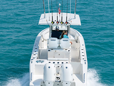 Rear view of white S 268 Sport center console boat with twin outboard engines and fishing rods.