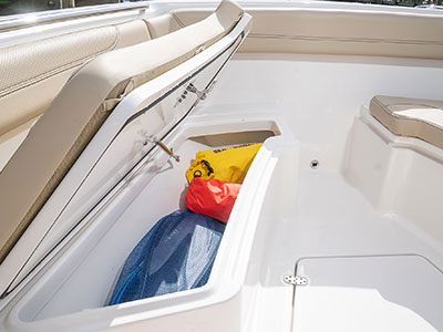 Detail of S 288 Sport boat port side forward seating storage with top open and dive gear inside.